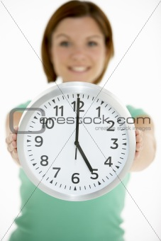 Woman Holding Clock Showing 5 O'Clock