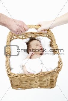 Newborn Baby Held In Basket By Parents