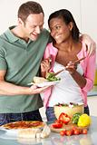 Young Couple Eating Meal In Kitchen