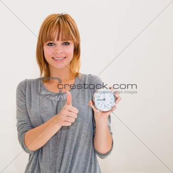 beautiful young woman holding alarm clock with thumbs up