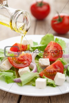 oil pouring over fresh salad