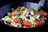 fresh pasta with tomatos and olives in a pan