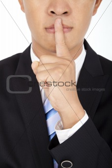 businessman showing quiet gesture with his finger