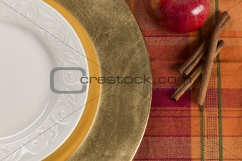 Abstract Fall Colored Table Setting of Apple and Cinnamon with Empty Plate.
