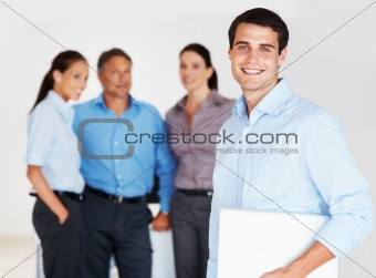 Handsome business man holding laptop and smiling