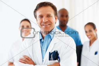 Smiling mature doctor with his team