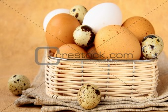 Group of brown and white hen's eggs in wicker basket