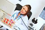 Concerned female medical doctor talking on phone and looking in monitor