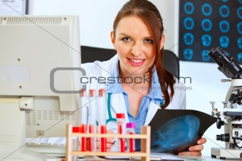 Happy doctor woman sitting at office table with patients roentgen