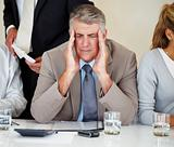 Elderly businessman having headache at meeting 