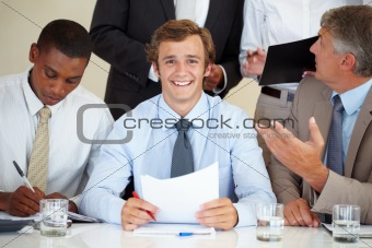Smiling young businessman with his colleagues at meeting
