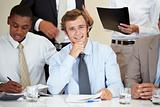 Young male executive sitting in a meeting with associates