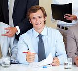 Confident young businessman signing a contract