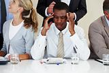 Afroamerican businessman suffering from headache during a meetin
