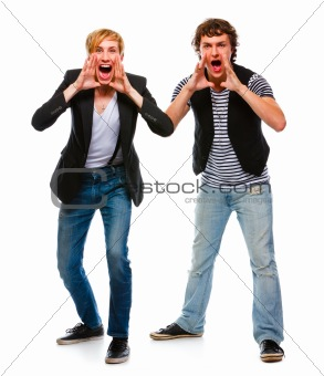 Two cheerful modern young men shouting through megaphone shaped hands