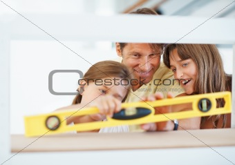 Father and daughter measuring angle of wooden board
