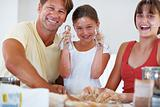 Family baking cookies in kitchen and smiling