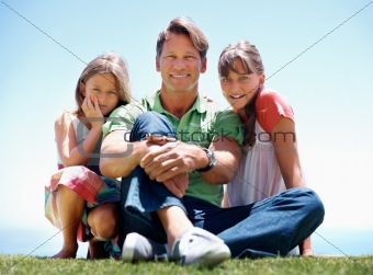 Man sitting on grass with his daughters
