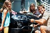 Family washing car and smiling