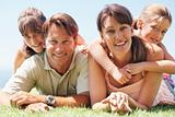 Family lying on grass and smiling