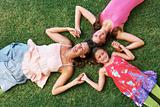 Mother and daughters lying on grass with heads together