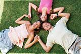 Family lying on grass with heads together