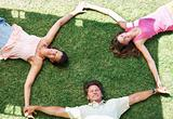 Family lying on grass holding hands