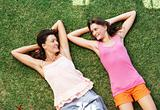 Mother and daughter relaxing on grass and smiling