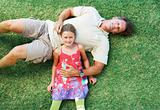 Father and daughter lying on grass