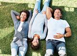 Man and woman relaxing on grass with daughter