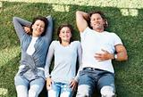 Family relaxing on grass and smiling