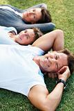 Man relaxing on grass with family