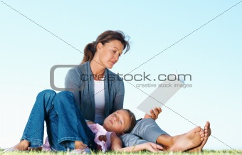 Woman reading book with daughter lying on her lap