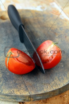 ceramic knife and tomato  on wooden table