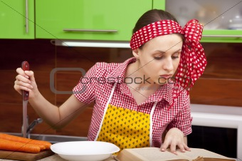 Woman in the kitchen with knife recipe book