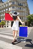 happy woman walking with shopping bags on crosswalk