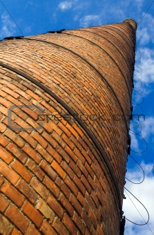 Huge brick chimney under blue sky - low perspective