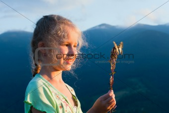 girl and butterfly in sunset mountain