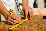 Worker Measuring Plywood