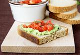sandwich with avocado and tomato on a wooden board
