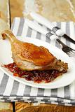 Roasted duck leg on white plate
