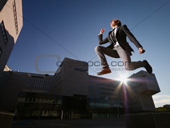 businessman jumping and smiling outside office