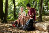 couple sitting on trunk and eating snack after trekking