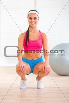 Happy fitness pretty girl squatting down