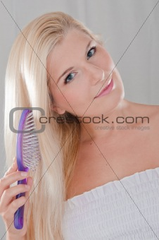 Beautiful woman with healthy blond hair brushing