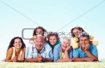 Cheerful Caucasian family lying on grass - copy space