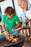 Grand father teaching grand son to barbeque vegetables