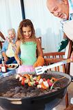 Grandfather and grand daughter barbecuing