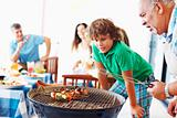 Grandfather and grandson barbecuing with family in the backgroun
