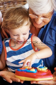 Little kid and grandmother playing with a toy